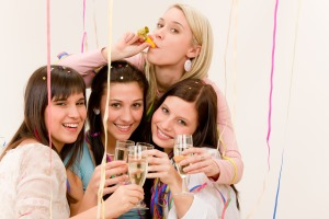 Birthday party celebration - four woman with confetti have fun